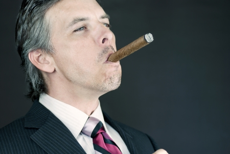 Close-up of a successful businessman enjoying a cigar.