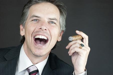 Close-up of a businessman celebrating with a cigar. photo