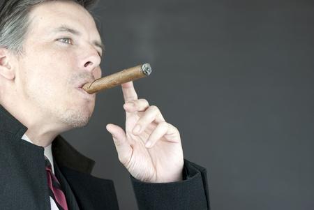 Close-up of a contemplative businessman smoking a cigar. photo