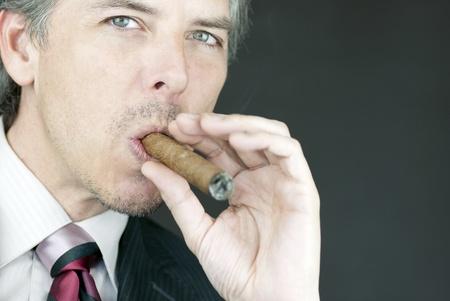 Close-up of a businessman smoking a cigar. photo