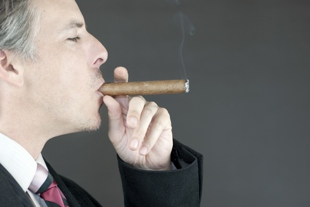 Close-up of a businessman smoking a cigar, side view. photo