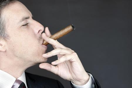 Close-up of a businessman smoking a cigar appreciatively. photo
