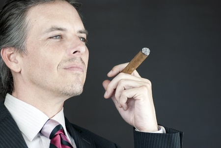 Close-up of a businessman holding a cigar in contemplation. photo