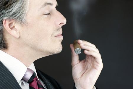 Close-up of a businessman smelling a cigar, side view. Standard-Bild