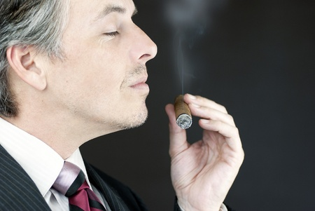 Close-up of a businessman smelling a cigar, side view. Stock Photo