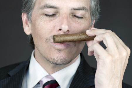 Close-up of a businessman smelling a cigar. Stock Photo