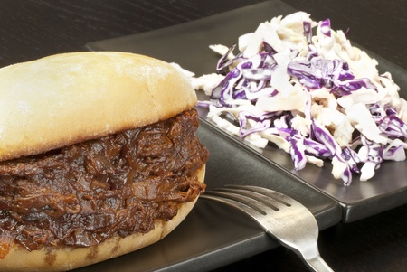 Close-up of pulled pork sandwich with coleslaw.