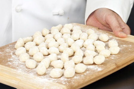 Close-up of a chef displaying freshly prepared gnocchi on a bamboo cutting board.