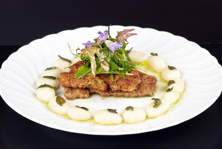 Close-up of plated pork cutlets with gnocchi, green oil and an arugula salad. photo