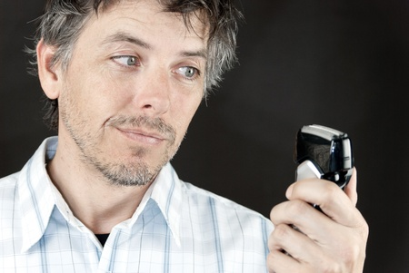 shaver: CLose-up of a man looking at his electric razor.