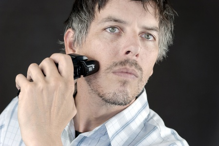 Close-up of a man using an electric razor to shave.
