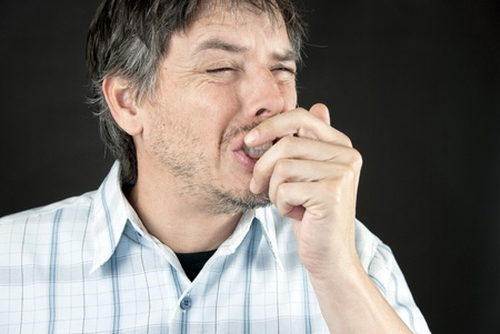 allergic reaction: Close-up of man sneezing into hand. Stock Photo