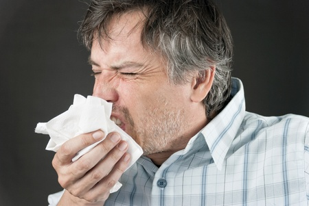 Close-up of a man sneezing into a tissue.