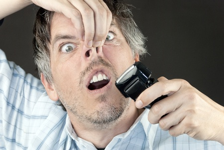 Cloe-up of a man attempting to trim his nose hair with a full sized electric razor.