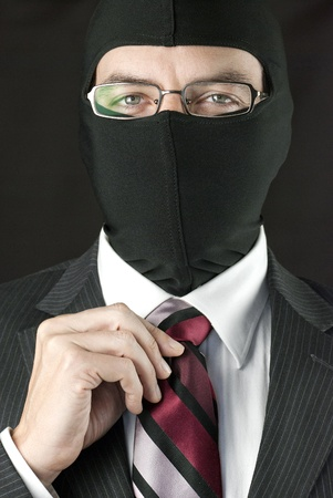 Close-up of a businessman wearing a balaclava straightening his tie. Stock Photo