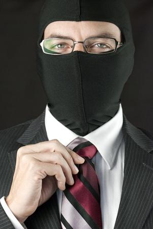 Close-up of a businessman wearing a balaclava straightening his tie. Standard-Bild
