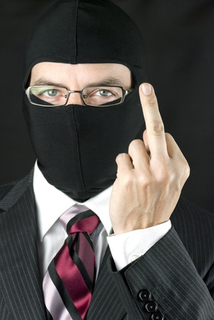 quiting: Close-up of a businessman wearing a balaclava giving the camera the finger.