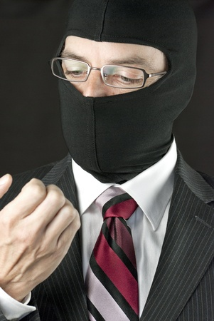 Close-up of a businessman wearing a balaclava inspecting his nails