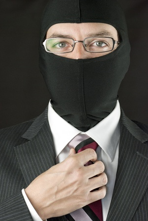 Close-up of a businessman wearing a balaclava adjusting his tie.