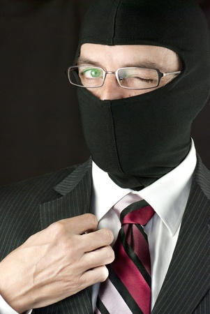 Close-up of a businessman wearing a balaclava winking at camera