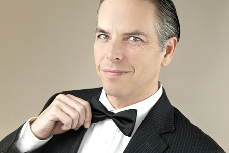 Close-up of a confident, smiling gentleman in a tux adjusting his bowtie with one hand. photo