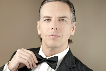 arrogant: Close-up of a confident gentleman in a tux adjusting his bowtie with one hand.