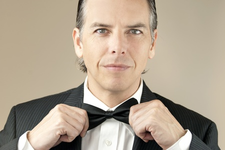 Close-up of a confident gentleman in a tux adjusting his bowtie with both hands.