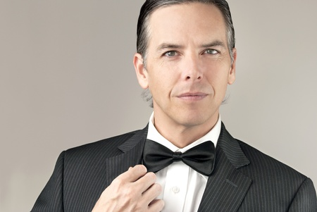 Close-up of a confident gentleman in a tux adjusting his cuff. Stock Photo
