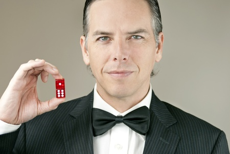 Close-up of a confident gentleman in a tux holding a pair of red dice showing seven. Banque d'images