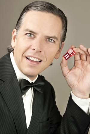 Close-up of a confident gentleman in a tux holding a pair of red dice showing seven, side shot. Banque d'images