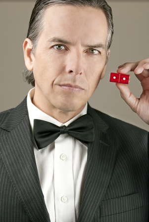 Close-up of a conerned gentleman in a tux holding a pair of red dice showing snake eyes. Banque d'images