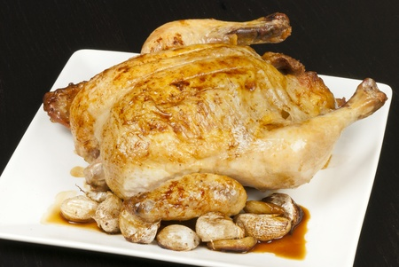jus: Close-up of a whole roasted heritage chicken surrounded by roasted garlic cloves and chicken jus. Stock Photo