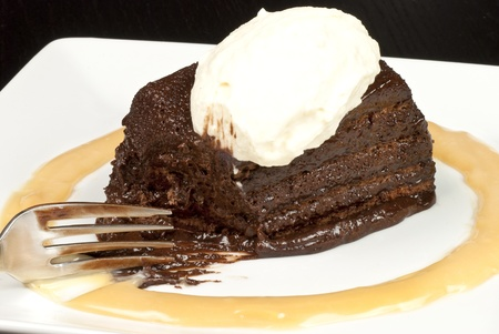 Close-up of a fork lying beside a chocolate marquise with a white chocolate marscapone and butterscotch sauce. Imagens