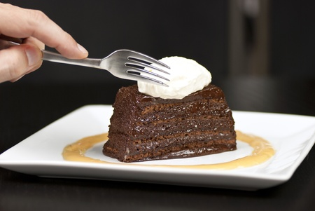 Close-up of a hand holding a fork about to slice into a chocolate marquise with a white chocolate marscapone and butterscotch sauce. Standard-Bild