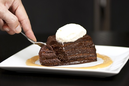 Close-up of a hand holding a fork slicing into a chocolate marquise with a white chocolate marscapone and butterscotch sauce. photo