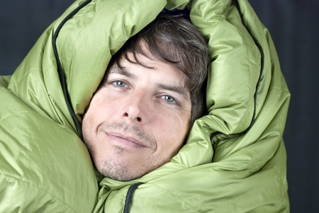 Close-up of a happy man wrapped up in a down mummy sleeping bag. 版權商用圖片
