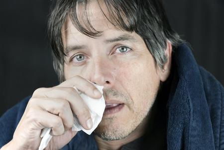 flu virus: Primer plano de un hombre enfermo en una bata de casa sec�ndose la nariz que moquea con un pa�uelo desechable.