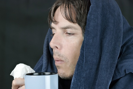 Close-up of a sick man holding a tissue blowing on a hot mug.