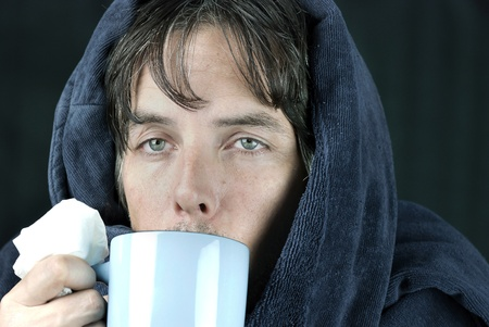 Close-up of a sick man holding a tissue drinking from a hot mug. Standard-Bild