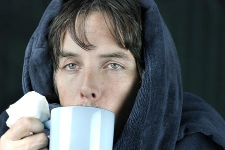 persona enferma: Primer plano de un hombre enfermo que sostiene un tejido de beber una taza caliente.