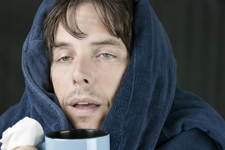 Close-up of a sick man holding a tissue and a hot mug.