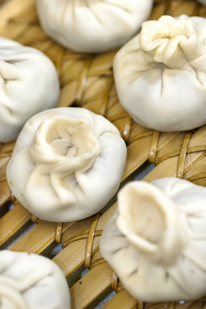 Close-up of a bamboo steamer filled with Tibetan style meatball and vegetarian momos ready to be steamed.