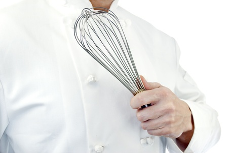 Close-up of a chef holding a whisk; side facing, torso only.