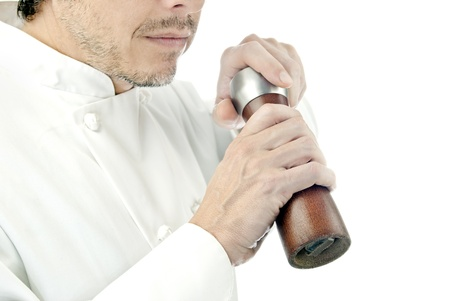 pepper grinder: Close-up of a chef using a pepper mill to season his food; side facing, torso only.