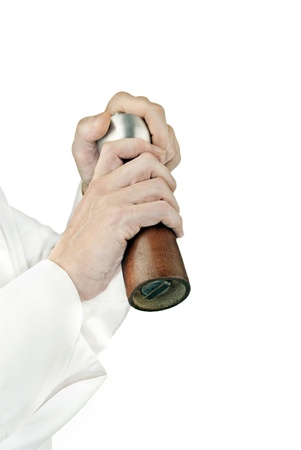 Close-up of a chef using a pepper mill to season his food; side facing, arms only.