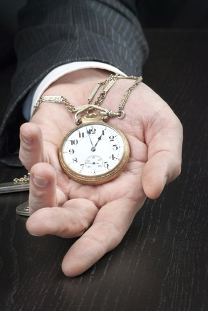 pocketwatch: Close-up of a businessman displaying an open pocketwatch in his hand. Stock Photo