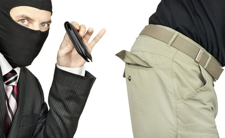 Close-up of a businessman wearing a balaclava picking the trouser pocket of a middle class man. photo