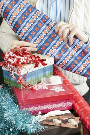 Close-up of a man unrolling wrapping paper for christmas presents. Stock Photo