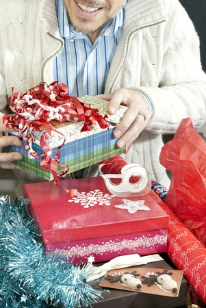 Close-up of a man surrounded by the accoutrements of christmas present wrapping. photo