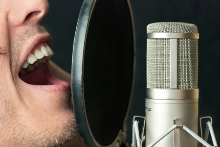 Super close-up of a man singing into a condenser microphone photo